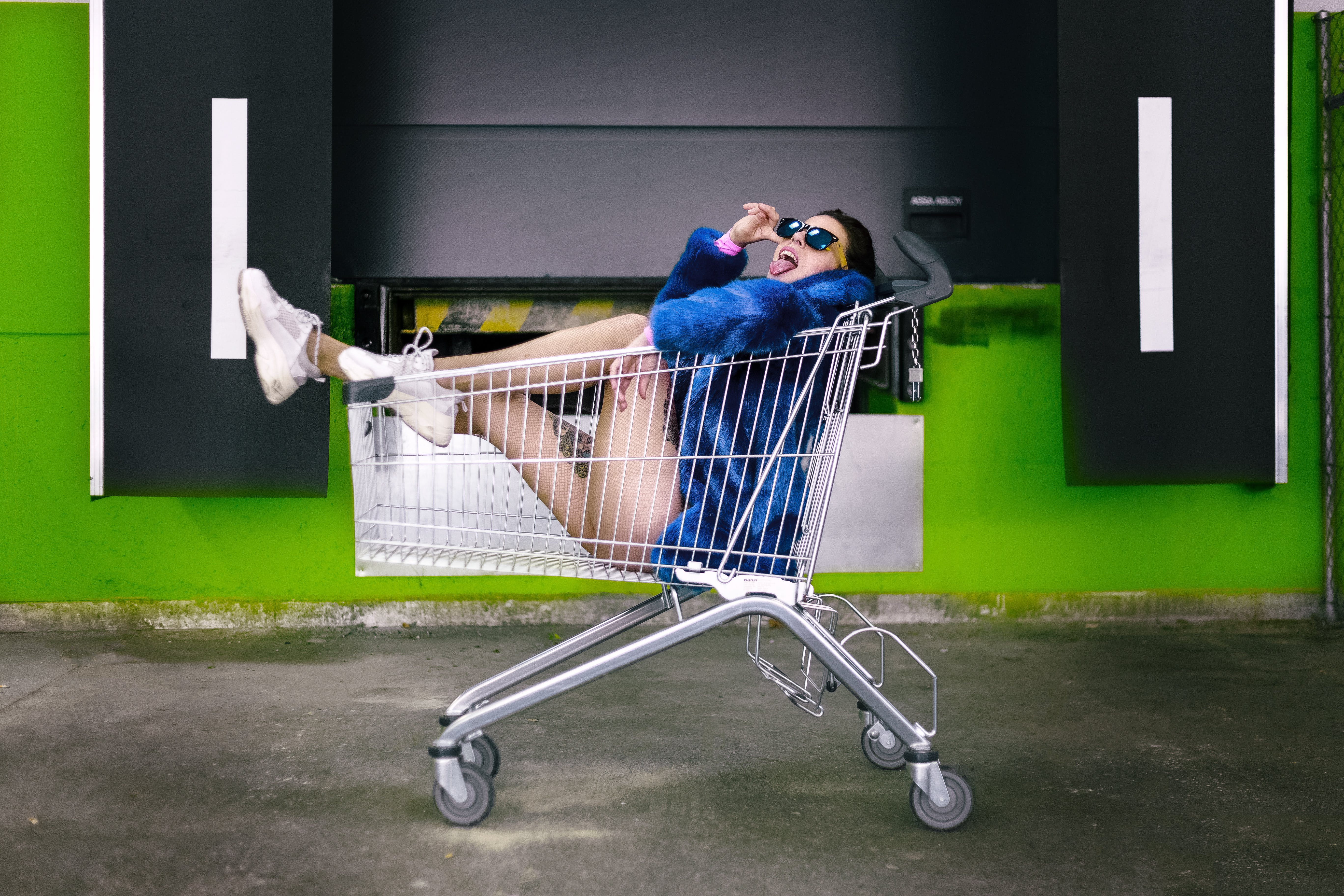 Photo of Woman Sitting Inside Shopping Cart Posing With Her Tongue Out