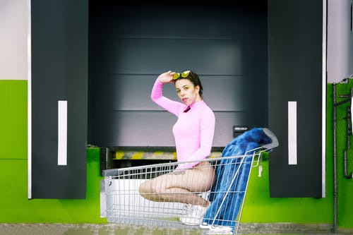 Woman Wearing Pink Swimsuit Riding Grocery Cart
