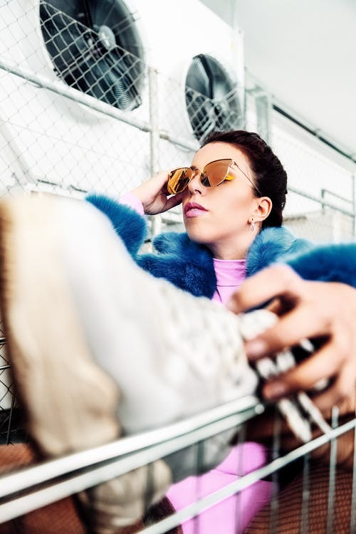 Woman Wearing Brown Sunglasses Holding Gray Shoe