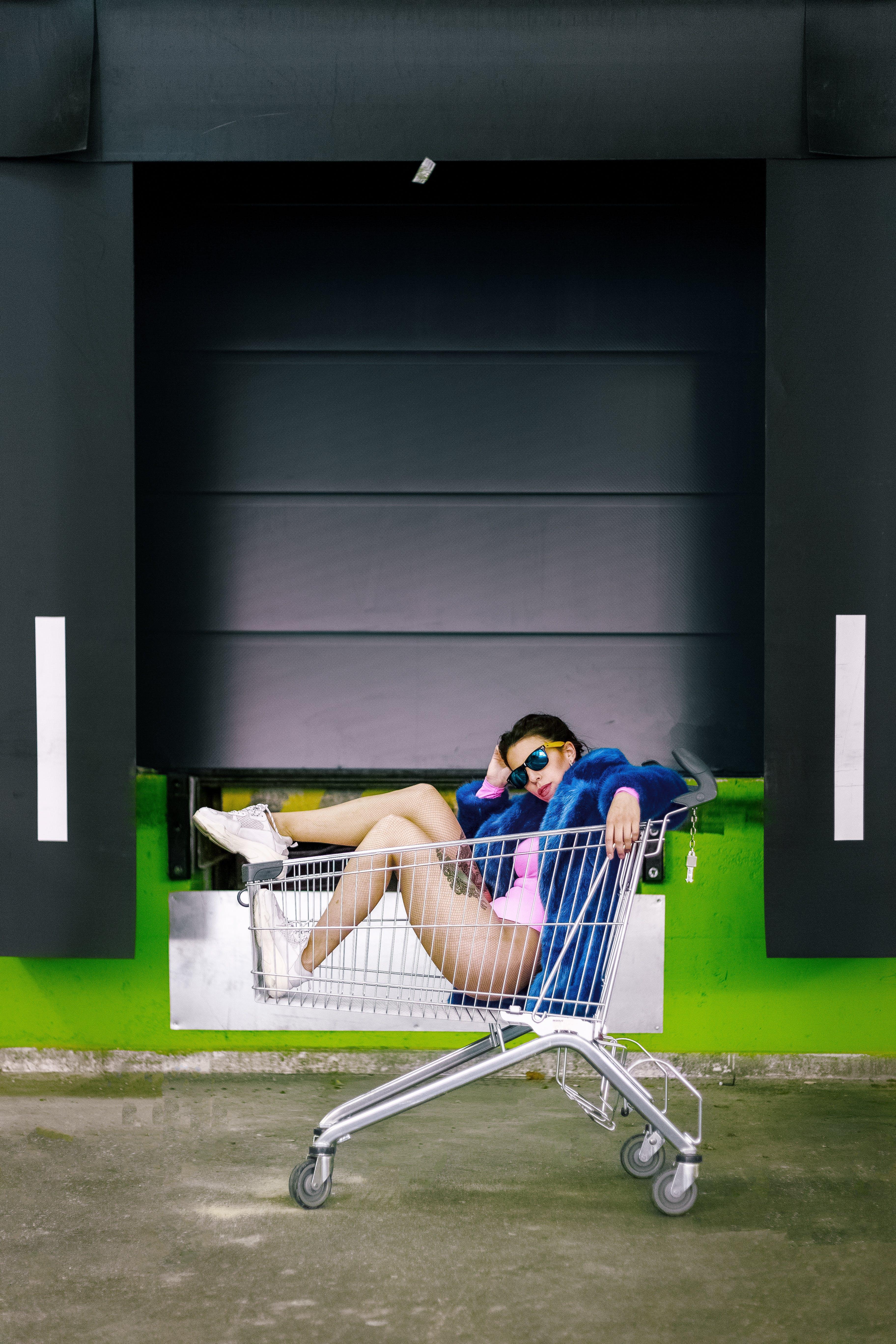 Photo of Woman Sitting Inside Shopping Cart Posing
