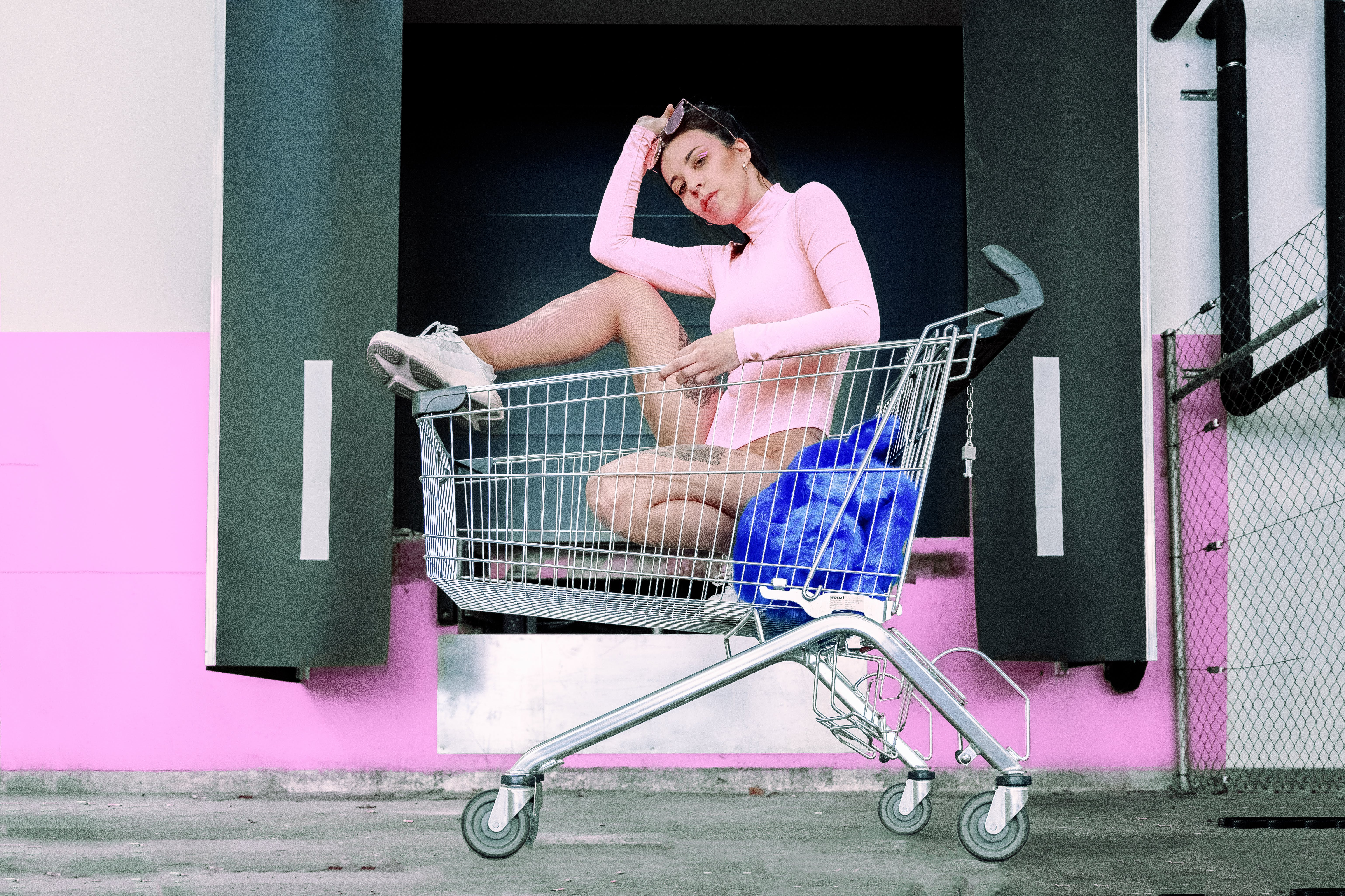 Photo of Woman in Pink Bodysuit Posing Inside a Shopping Cart