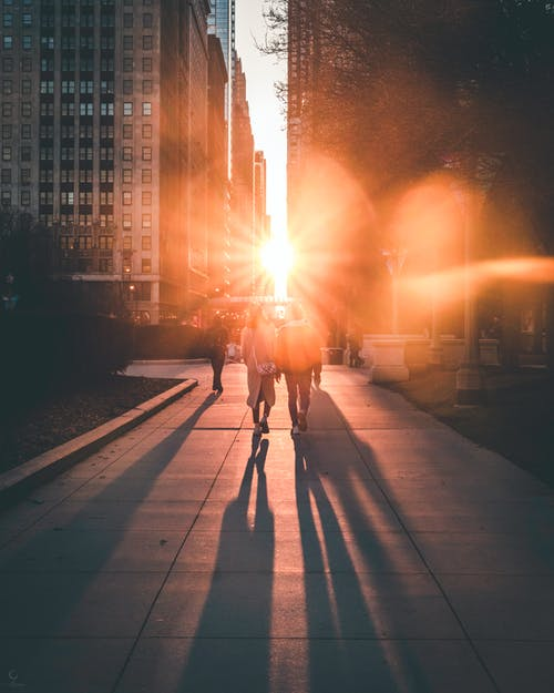 People Walking Down The Street With Ray Of Sun Between Two Buildings