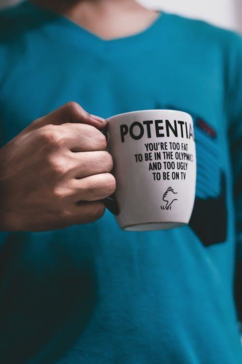 Person in Teal Shirt Holding White Ceramic Mug