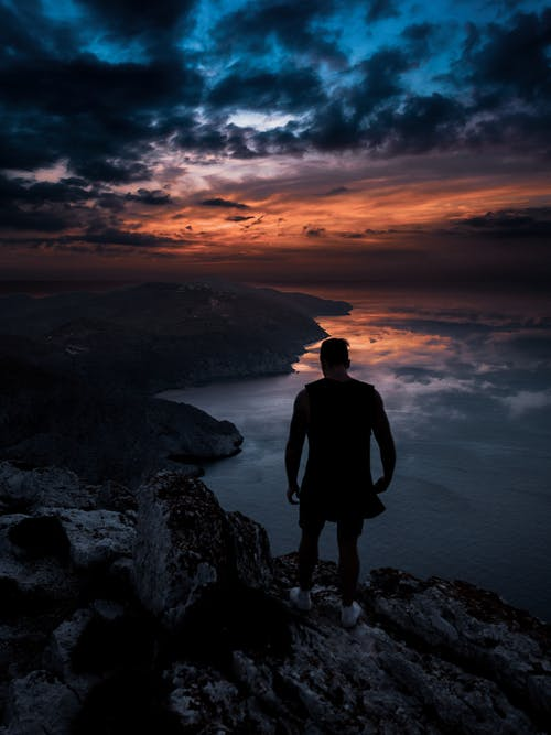Photo of Man Standing on Cliff