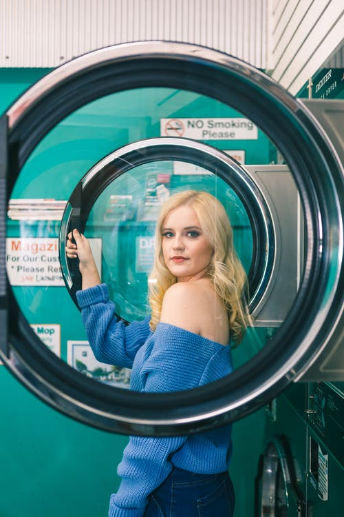 Woman in Blue Off-shoulder Long-sleeved Shirt Standing Beside Washing Machine
