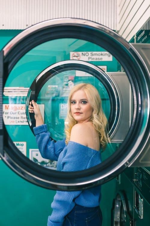 Woman in Blue Off-shoulder Long-sleeved Shirt Standing Beside Washing Machine