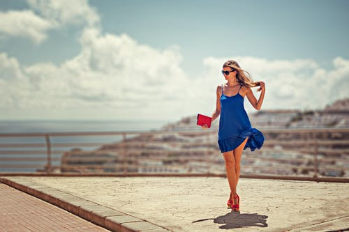 Woman In Blue Dress Carrying Red Purse