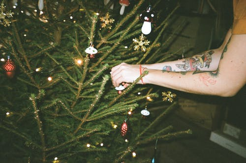 Person With Arm Tattoos Decorating Christmas Tree