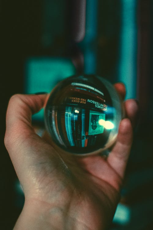 Person Holding Glass Sphere