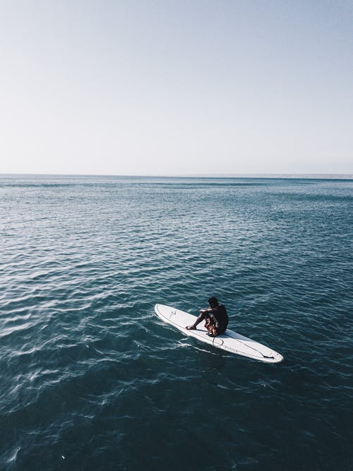 Man Riding White Surfboard In The Middle Of Ocean