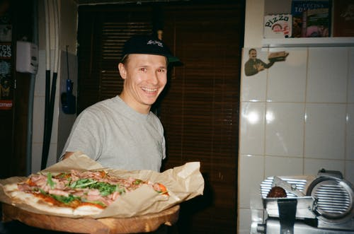 Man Standing and Smiling While Holding Pizza