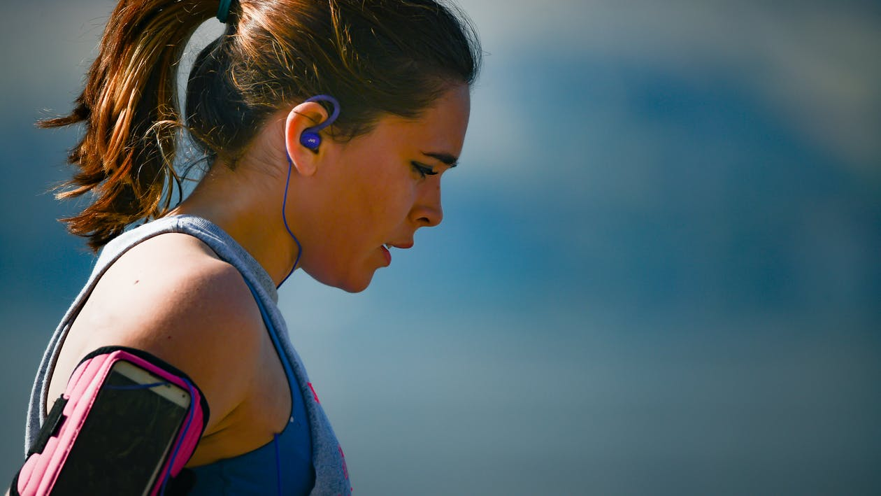 Woman Wearing Smartphone Armband And Blue Earphones