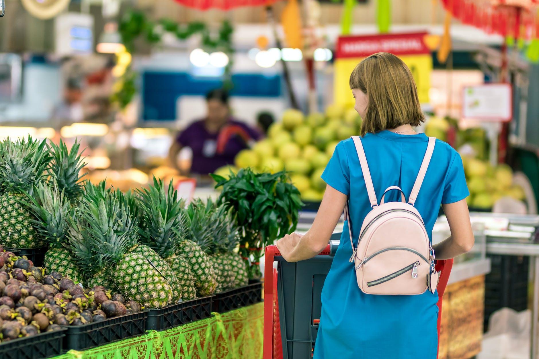 Vrouw met blauwe jurk met een supermarktkarretje doet boodschappen met een boodschappenlijstje.