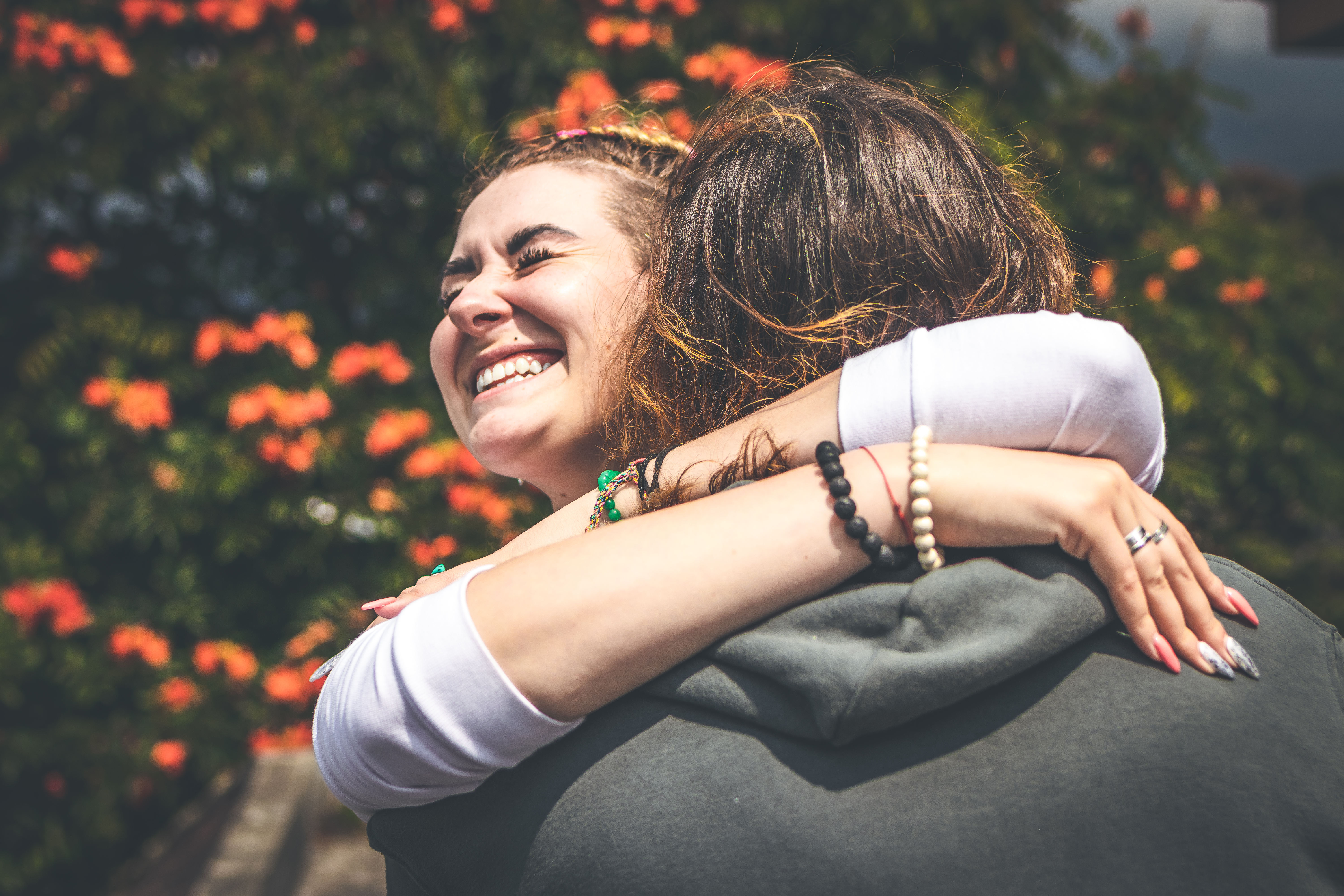 Smiling Woman Hugging Another Person