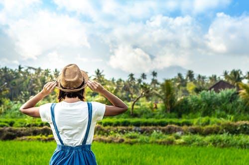 Wanita Berdiri Di Depan Lapangan Hijau