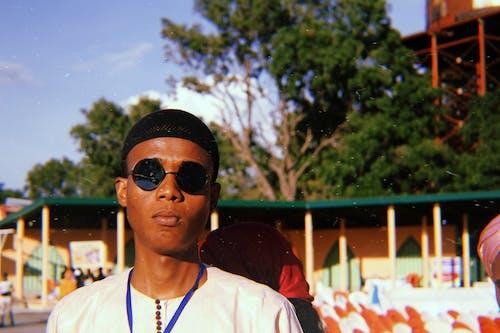 Kostenloses Stock Foto zu afrikanischer junge, baum, brillen, draußen