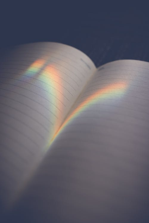 Empty opened diary with blank pages and reflection of bright rainbow light on surface