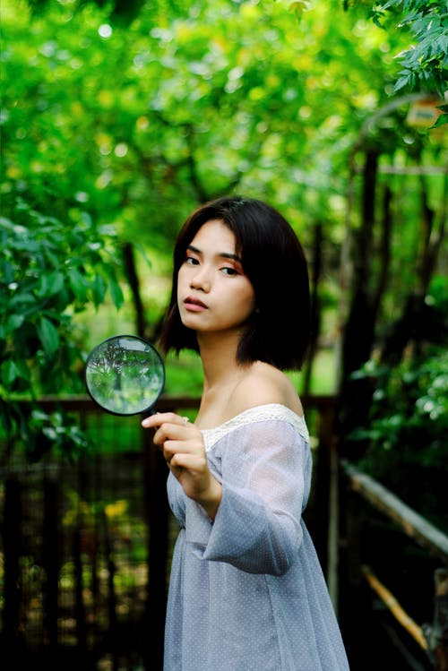 Photo Woman in White Off-shoulder Dress Holding Magnifying Glass