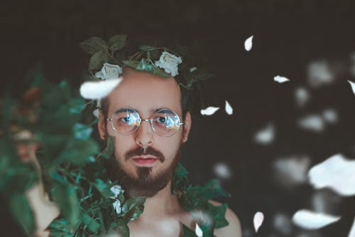 Selective Focus Photography of Man Covered With Green Vine Plant