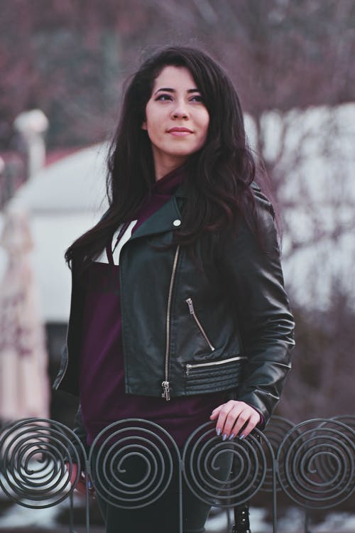 Photo of Woman in Black Leather Jacket Holding Gray Metal Railings