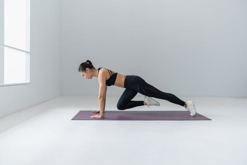 Woman Doing Exercises on Purple Mat Inside White Painted Room
