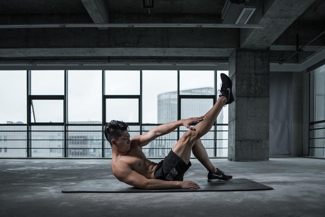 ヨガマットで運動しているトップレスの男性の写真