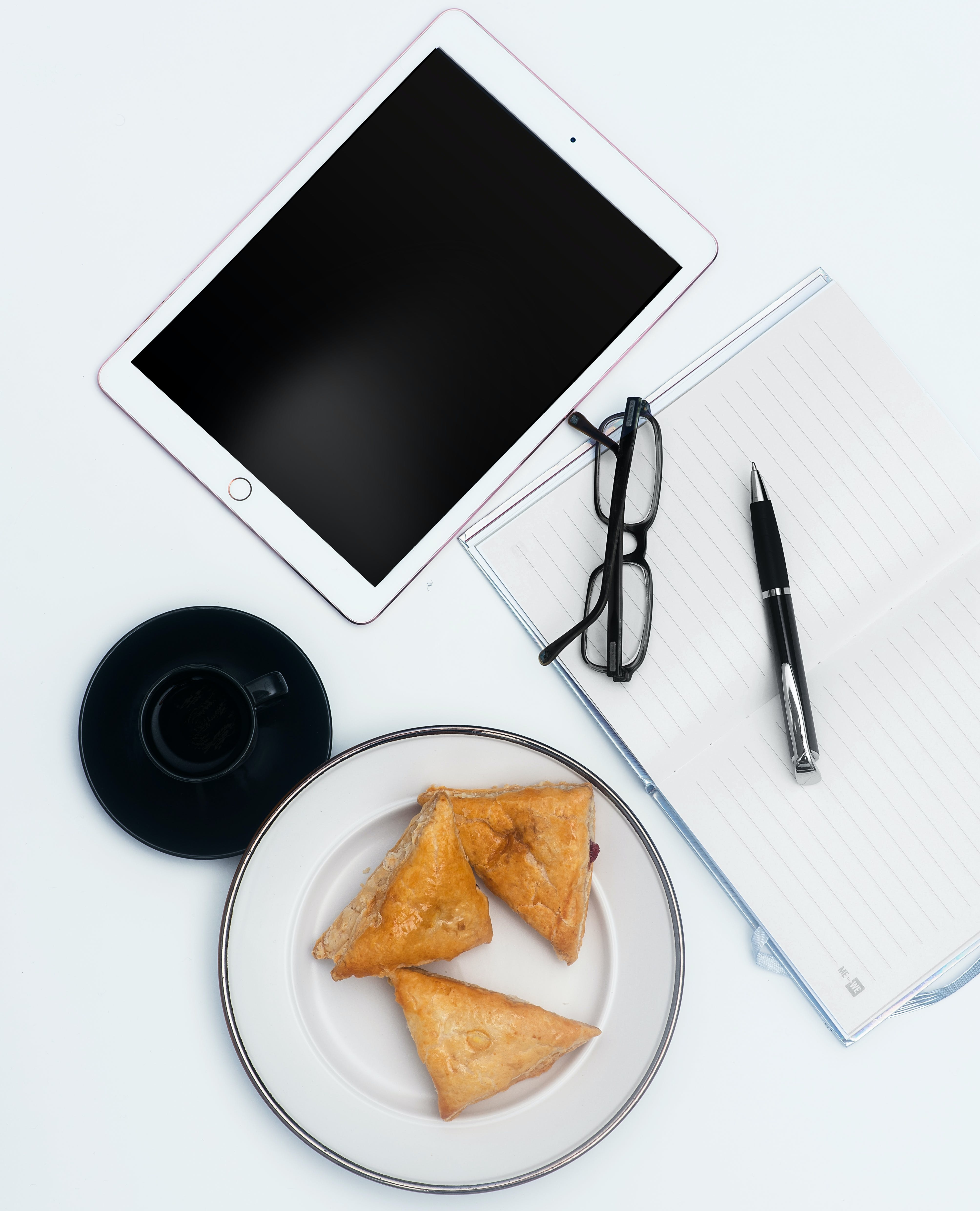 White Ipad and Items on White Surface