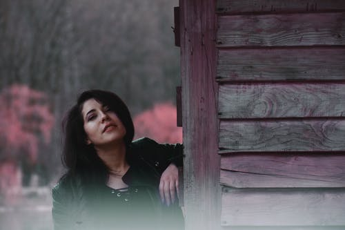 Woman Leaning on Purple Wood