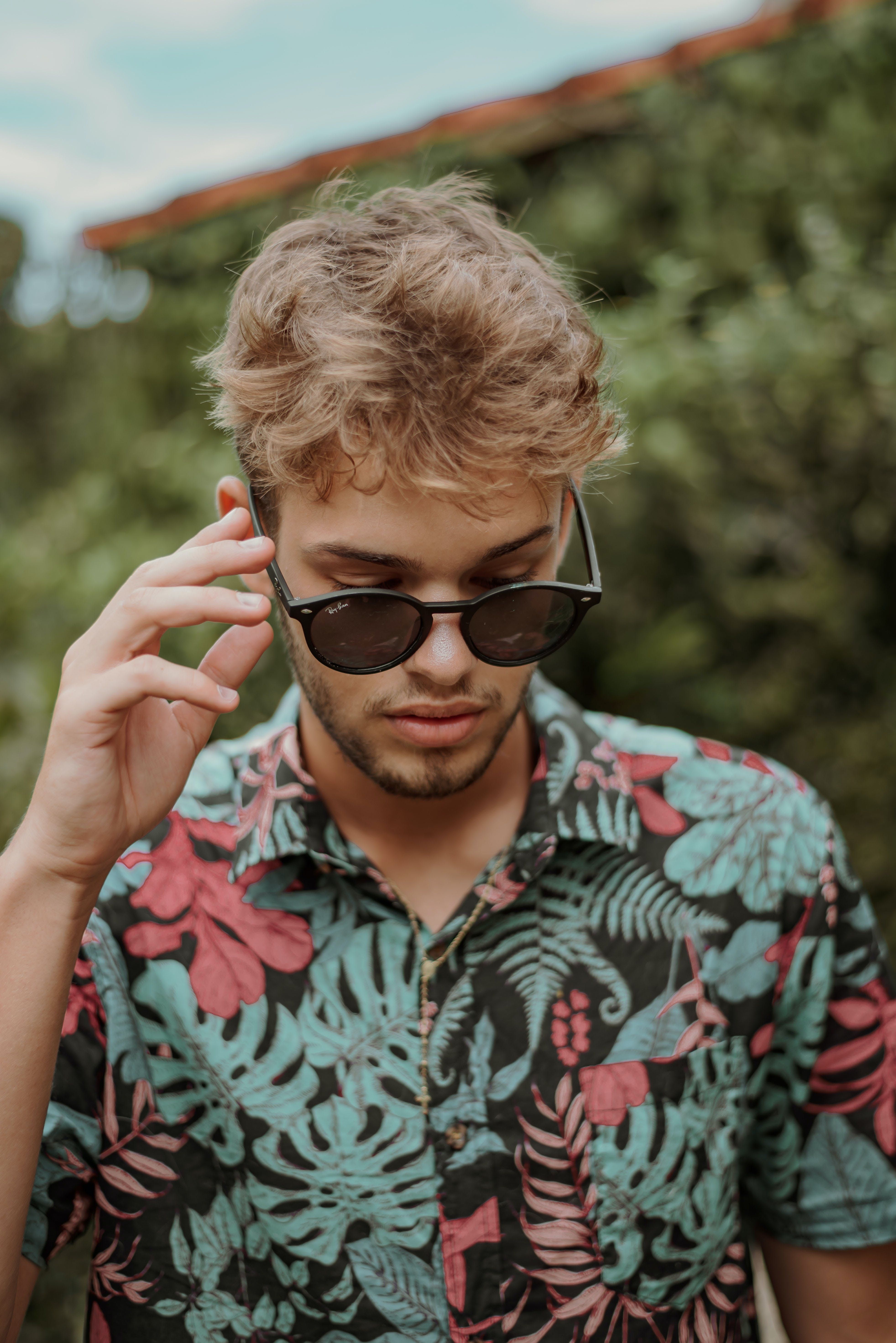 Man Wearing Floral Polo Shirt Holding Sunglasses