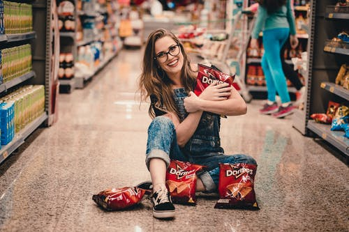 Photo of Smiling Woman Sitting in the Middle of Shopping Aisle Holding Dorito Chips