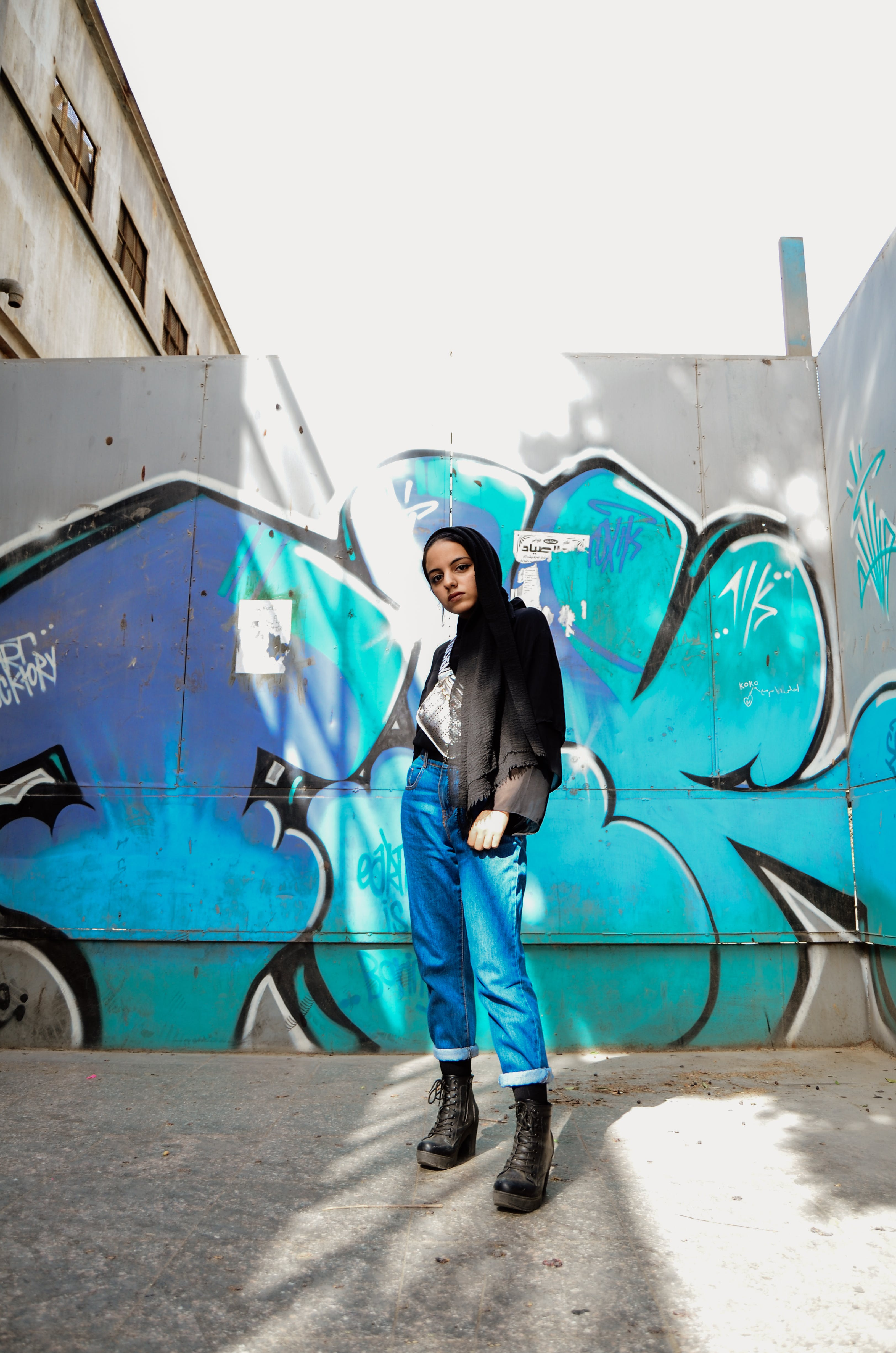 Photo of Woman Standing in Front of Graffiti Wall
