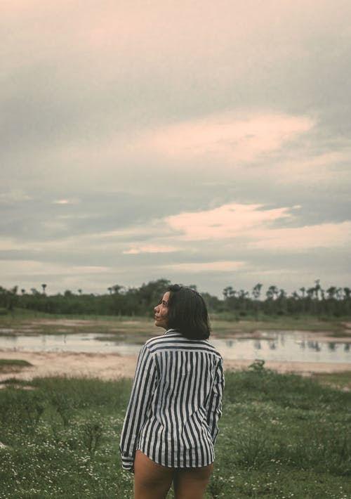 Calm black woman in cloudy countryside