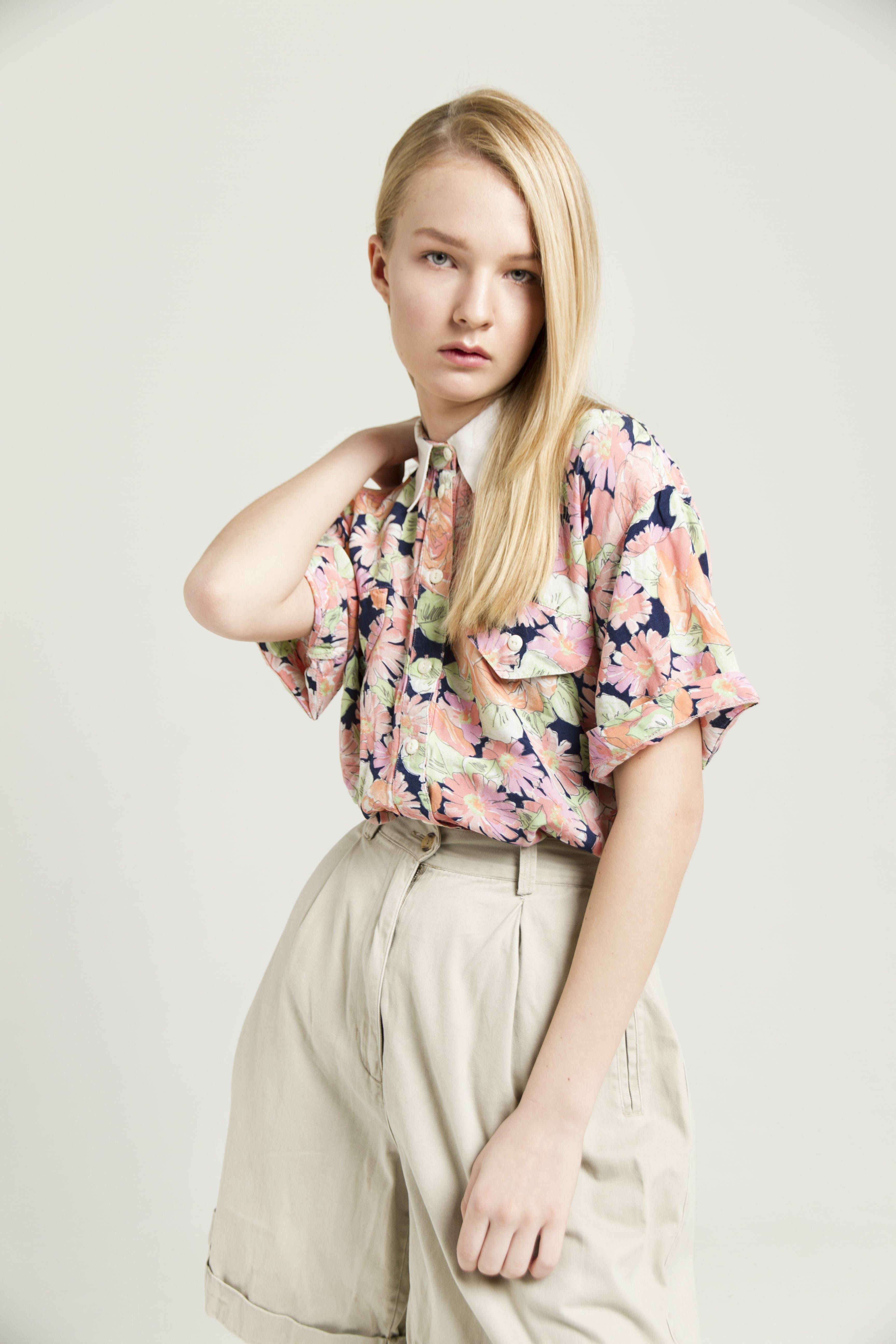 Photo of Woman in Floral Shirt and Beige Shorts Posing