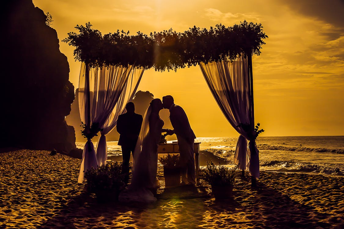 Silhouette Photography of Newly Wed Kissing on Seashore