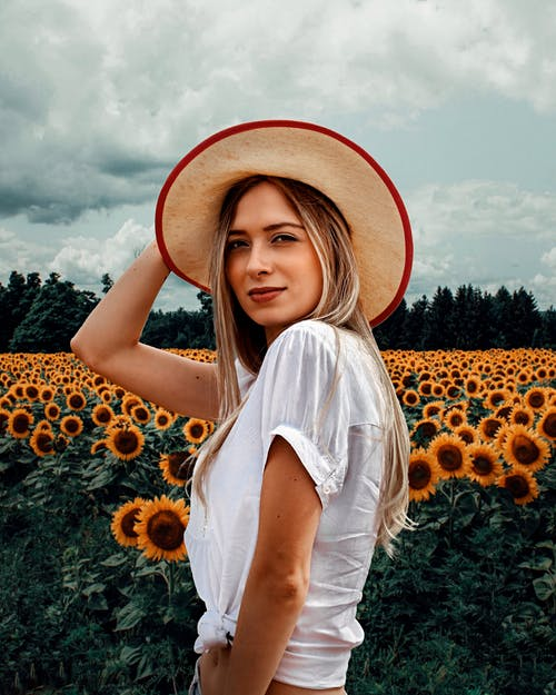 Photo of Woman in White Short-sleeved Crop-top and Brown Sun Hat Posing by Sunflower Field