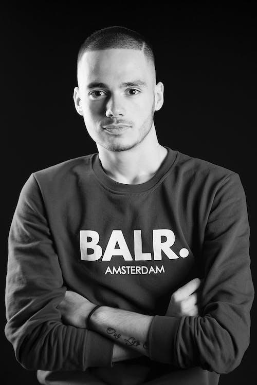 Portret W Skali Szarości Zdjęcie Mężczyzny W Bluzie Z Założonymi Rękami