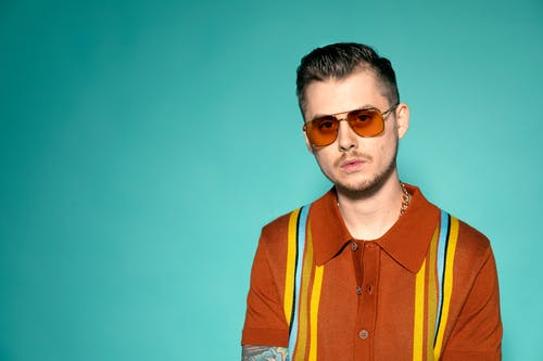 Portrait Photo of Man in Sunglasses and Brown and Yellow Polo Shirt Standing In Front of Blue Background