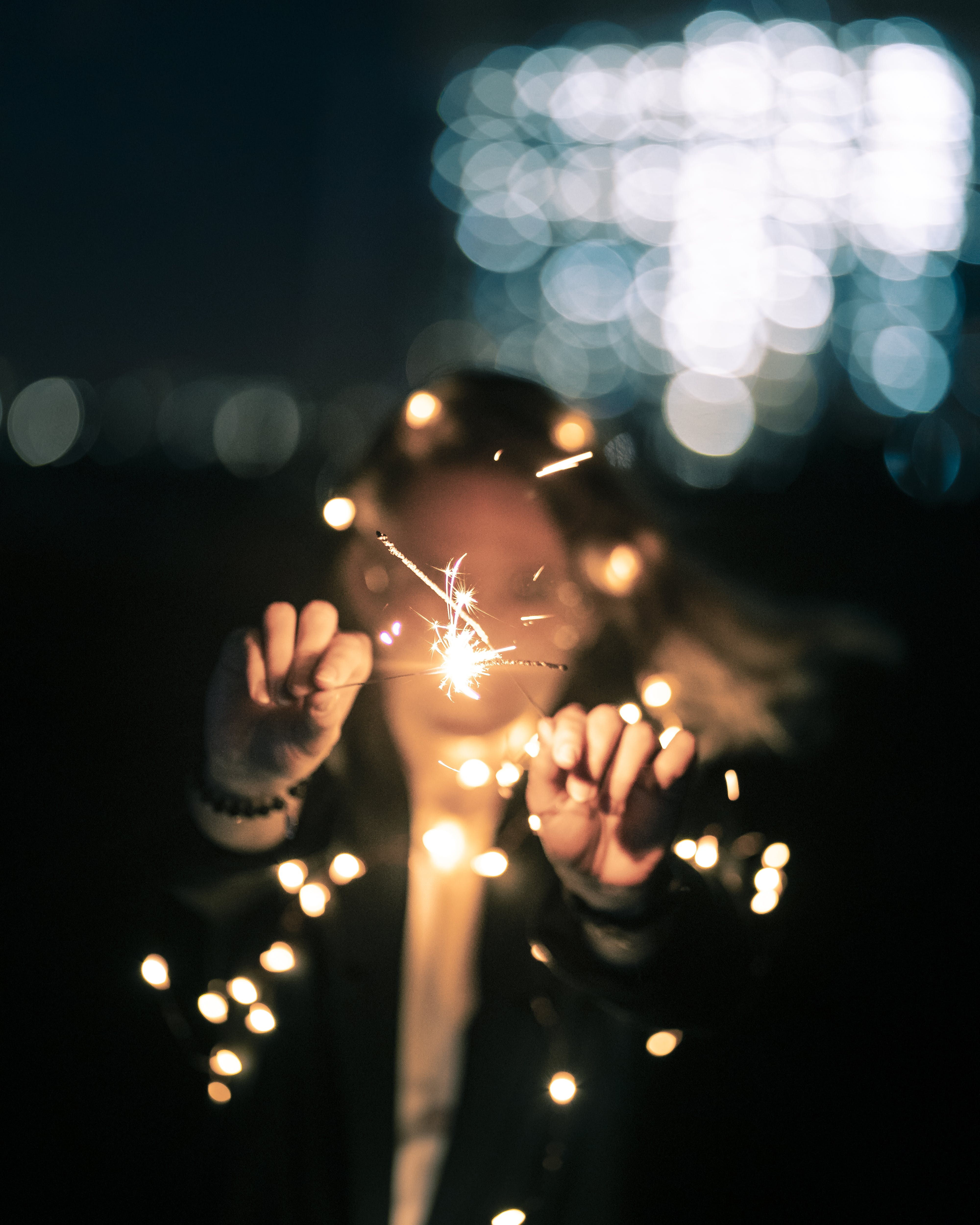 Selective Focus Photo of Woman Holding Sparklers at Night