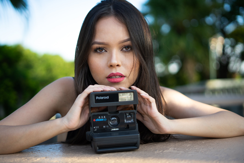 Portrait of Woman Holding Gray Polaroid Camera
