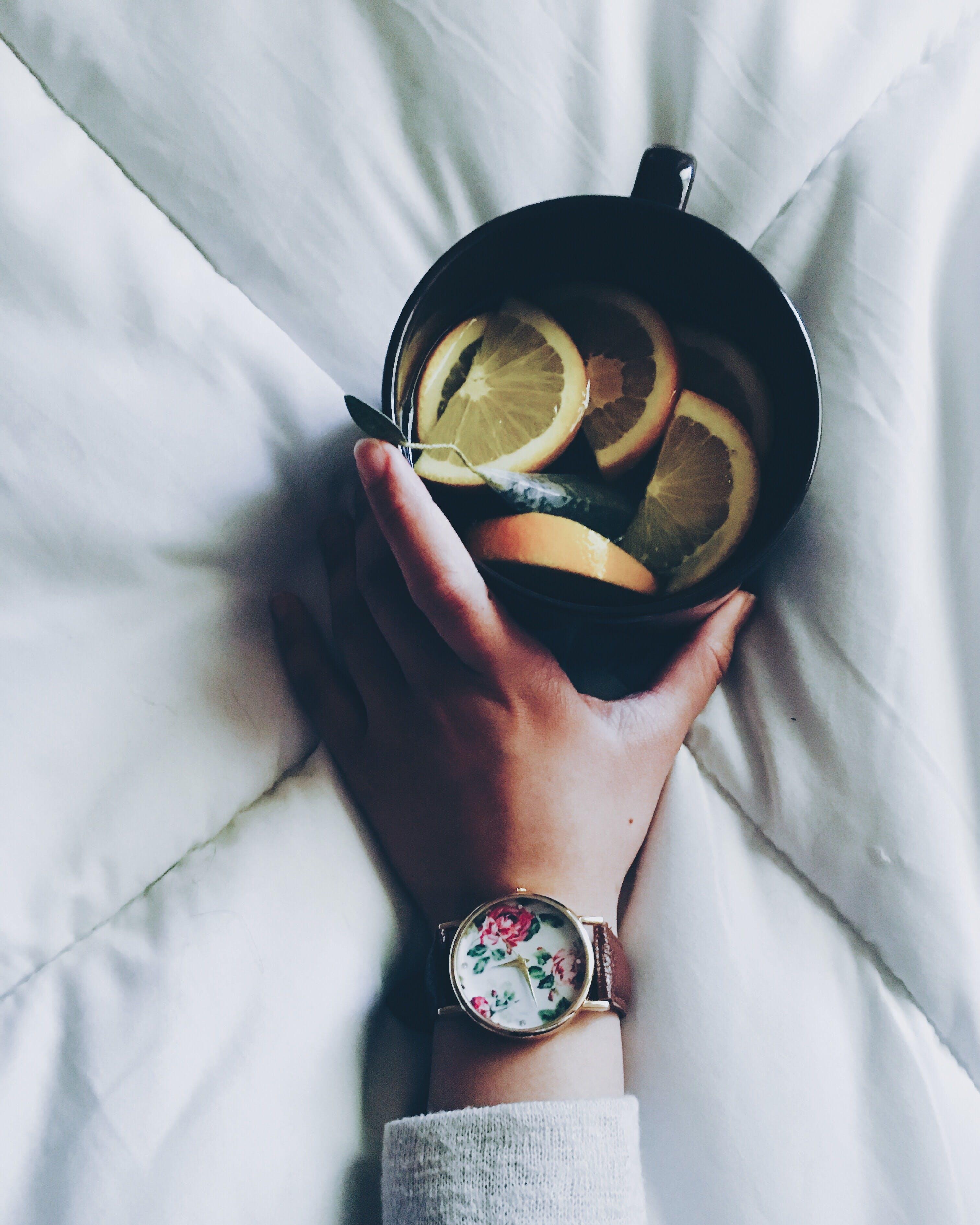 Woman Holding Black Ceramic Mug With Sliced Lemon on Top of White Bed Comforter