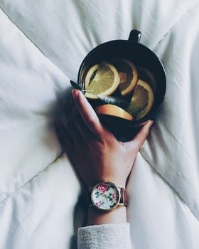 Woman Holding Black Ceramic Mug With Sliced Lemon on Top of White Bed Comforter