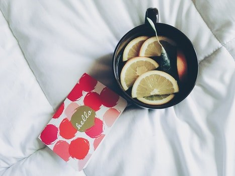 Black Ceramic Mug Filled With Sliced Orange Near Cards