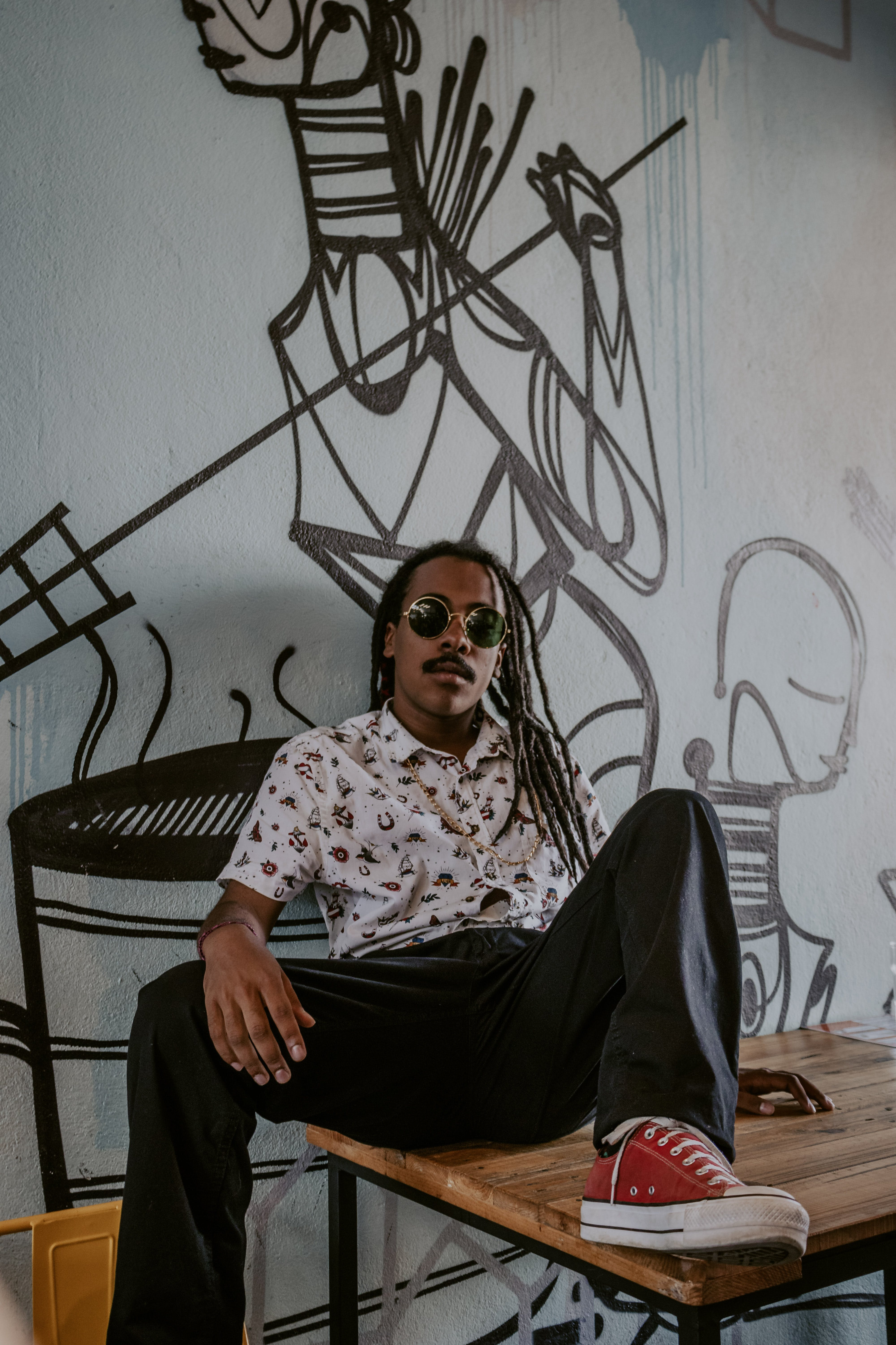 Man in White Shirt and Black Pants Sitting on Table While Leaning on Wall