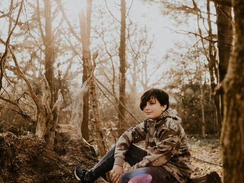 Boy in Brown and Black Camouflage Hoodie Sits on Tree