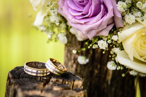 Close-up Photography of Wedding Rings Near Purple Rose