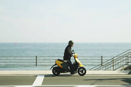 Man Riding Yellow Motor Scooter Sur Route