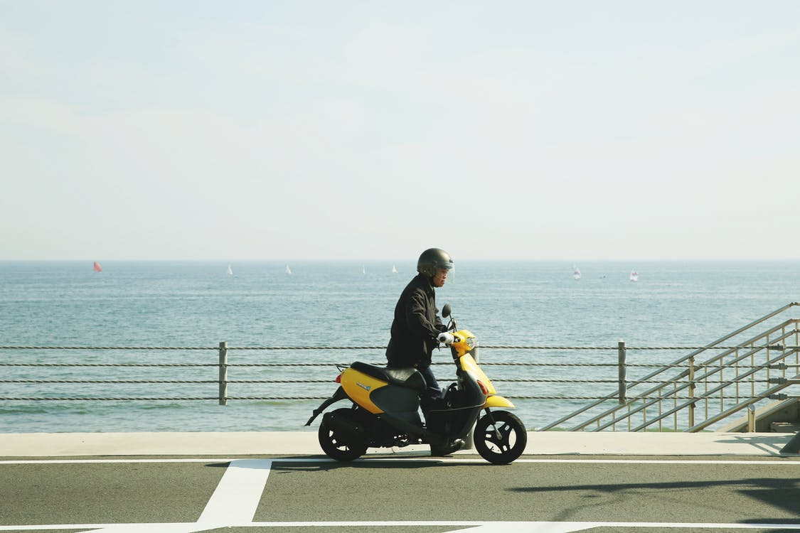 Man Riding Yellow Motor Scooter on Road