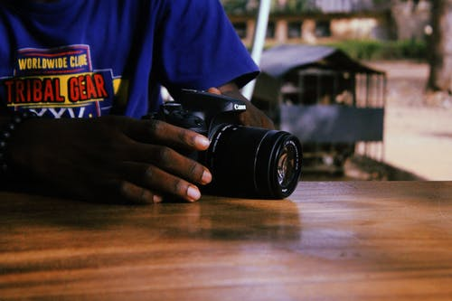Person in Blue Printed Shirt Holding Canon Dslr Camera
