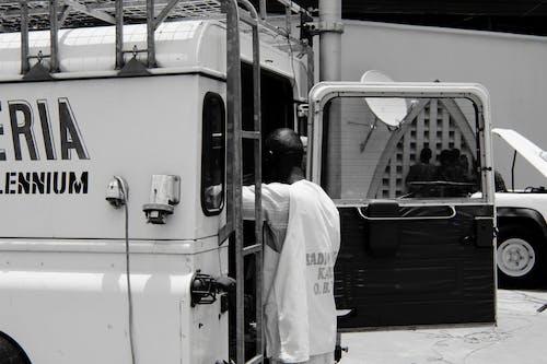 Fotografía En Escala De Grises De Un Hombre Parado Detrás De Un Camión Utilitario