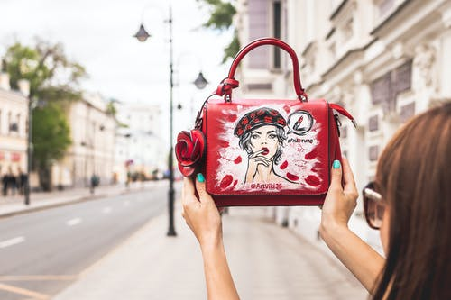 Woman Holding Her Red and White Leather Handbag Up High at the Sidewalk